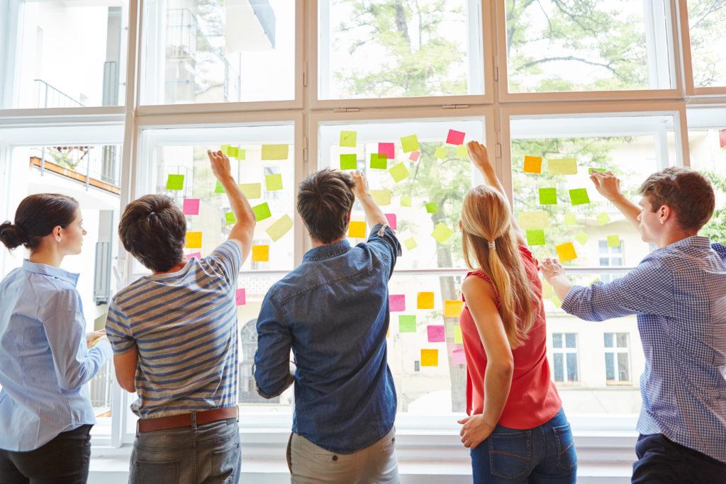 Junge Studenten im Seminar für Brainstorming mit bunten Zetteln