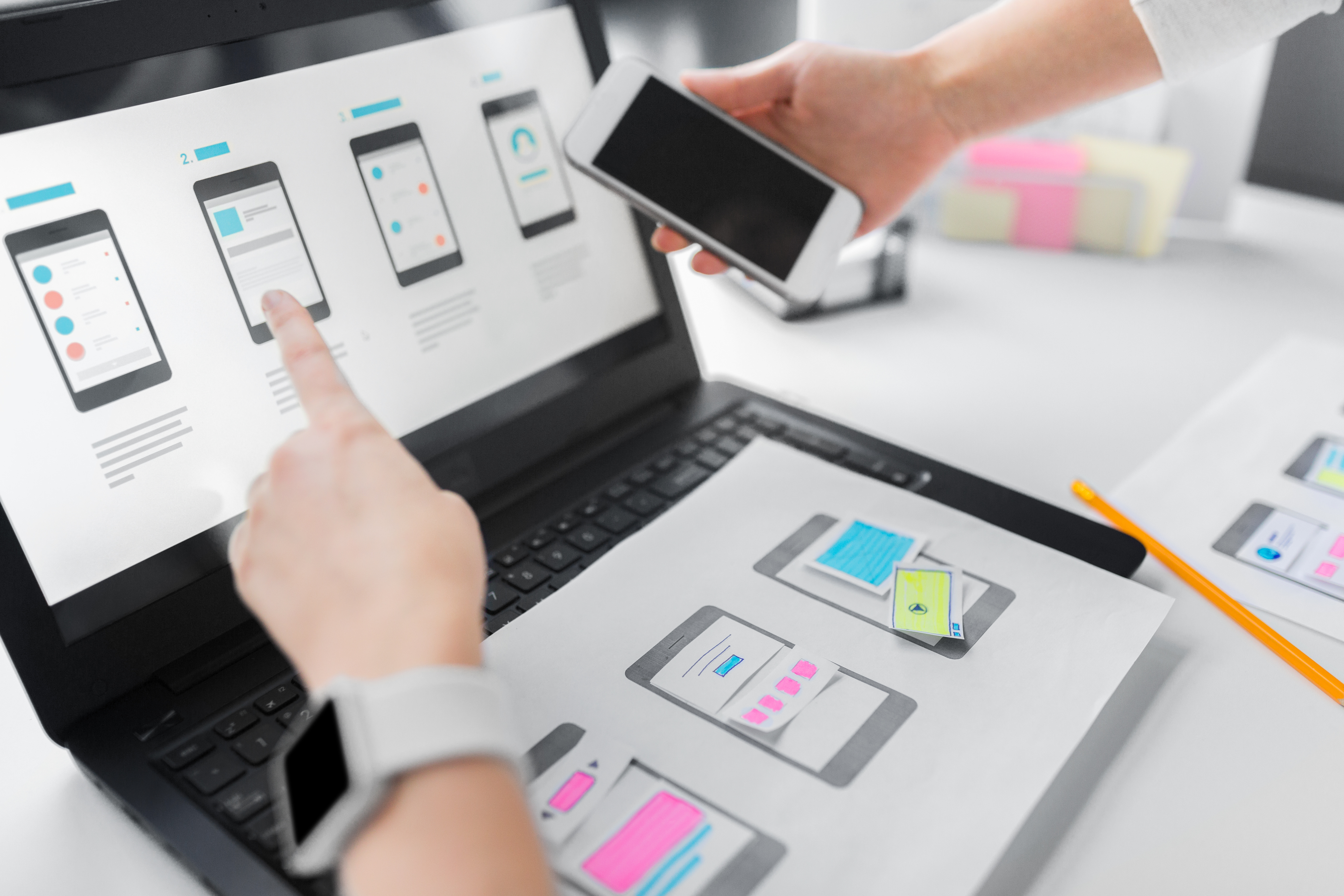 app design, technology and business concept - web designers or developers with laptop computer and smartphone working on user interface layout at office